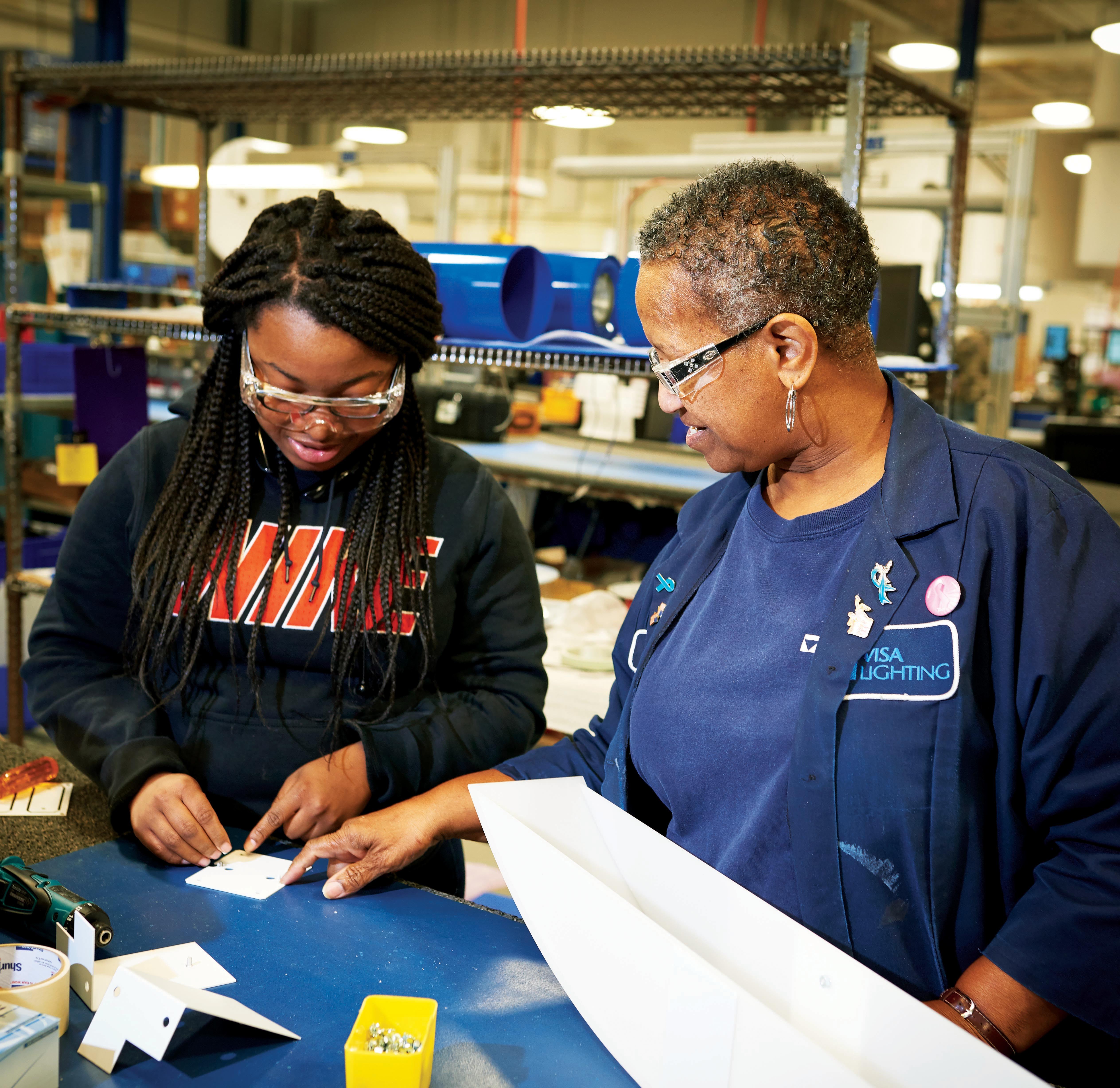 Visa lighting represents made in America manufacturing, Alice and her granddaughter work together in assembly.