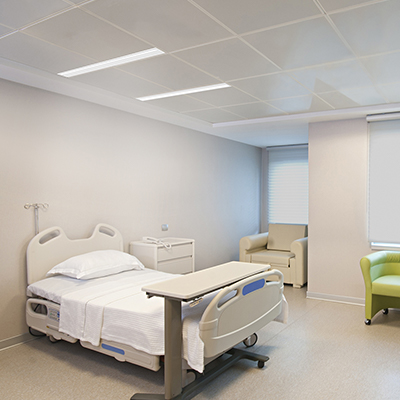 Lenga asymmetric slots emit light onto the patient bed without taking up valuable plenum space