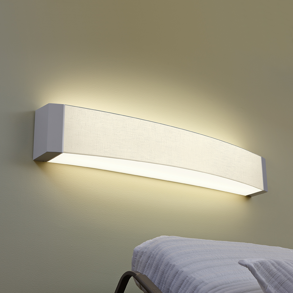 A curved linear headwall luminaire behind a patient bed