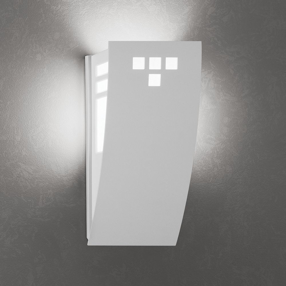 A wedge-shaped curved wall sconce with cutout accents in its solid body and uplighting