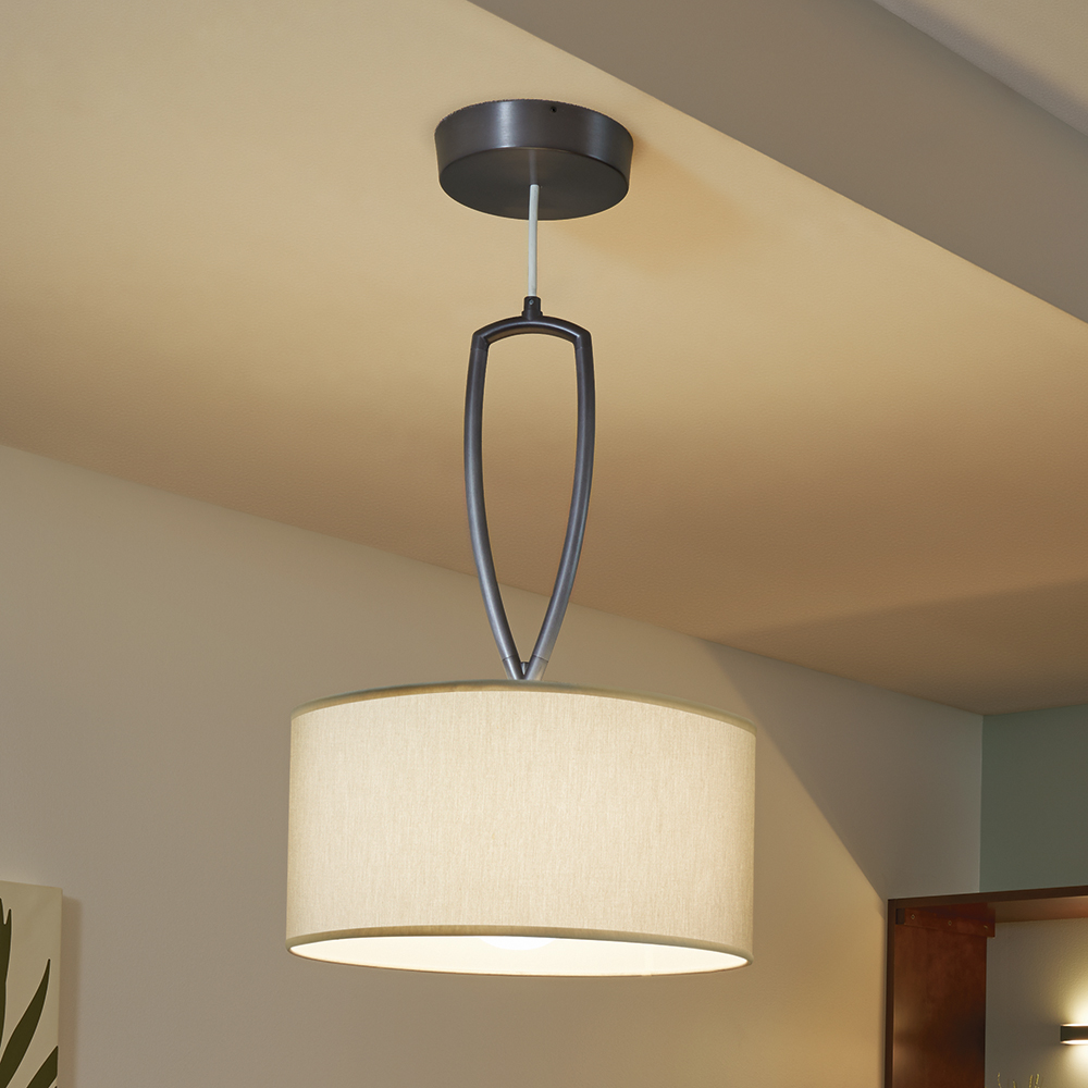 A hanging luminaire with a cylindrical fabric shade and a curved metallic mounting accessory