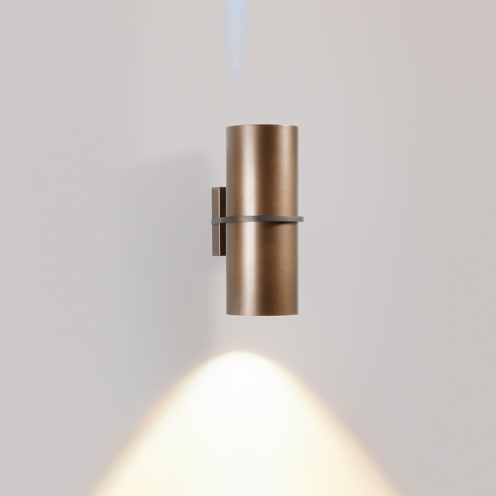 A cylindrical outdoor wall sconce with one round accent