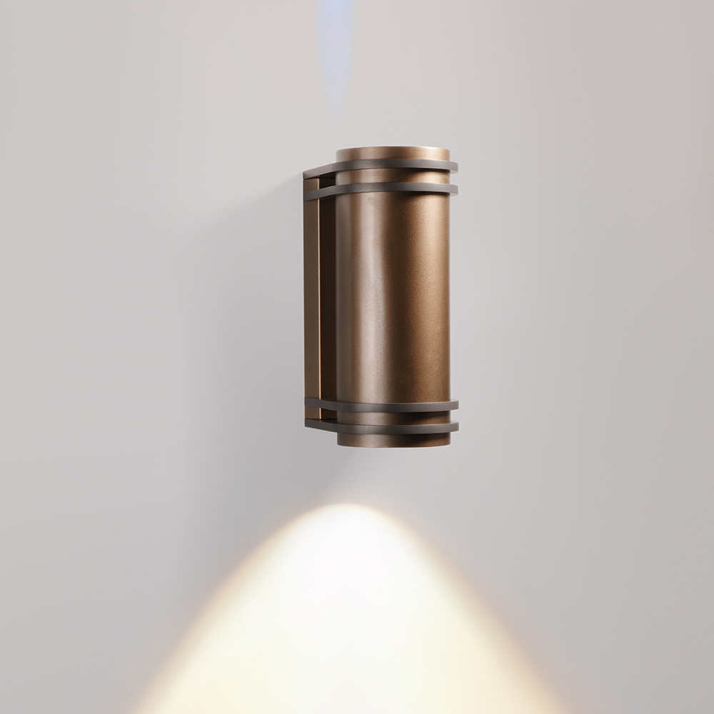 A cylindrical outdoor wall sconce with four round accents