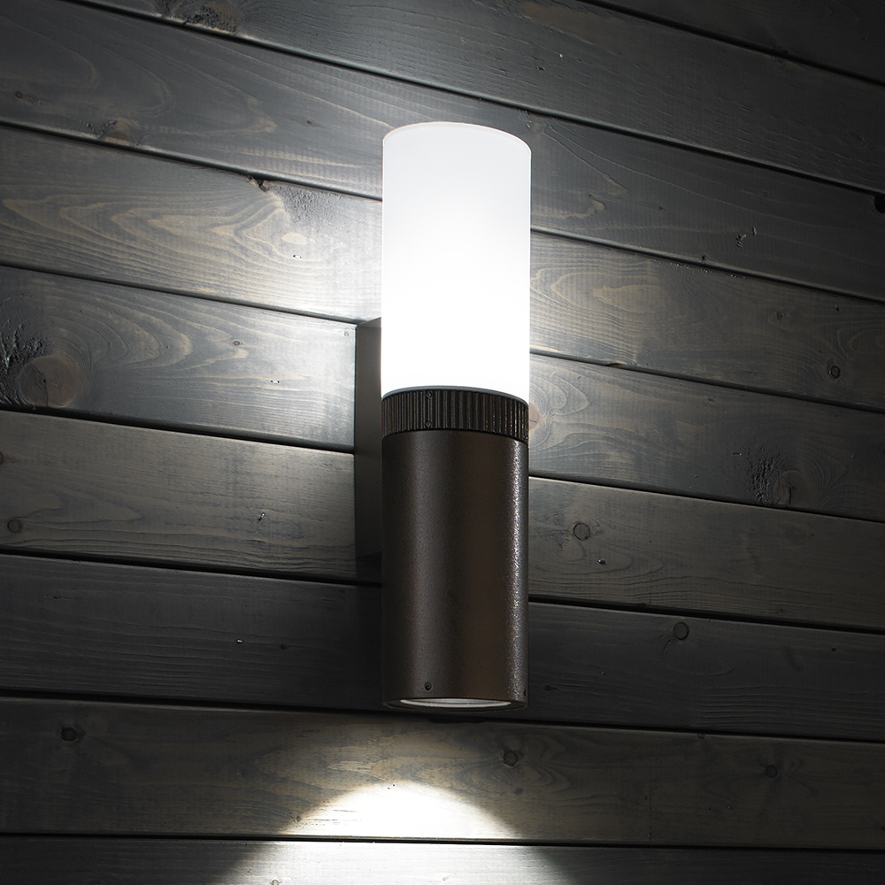 An outdoor wall sconce with a cylinder body that's solid on the bottom and luminous on the top, with a downlight