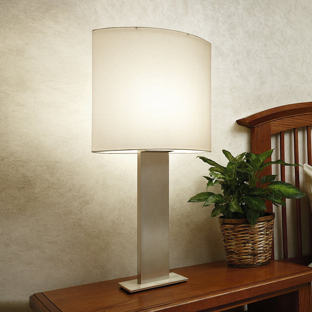 A medical table lamp with a square fabric-like shade on a patient room table