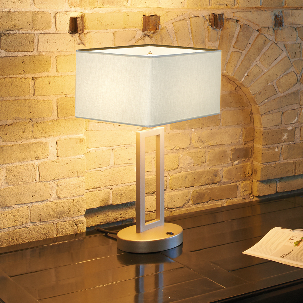 A square-shaded table lamp on a wooden desk in front of a brick wall