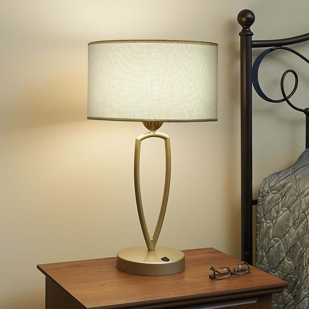 A round-shaded lamp on a bedside table