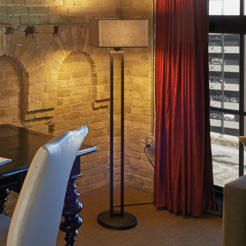 A floor lamp with a square shade next to a red curtain
