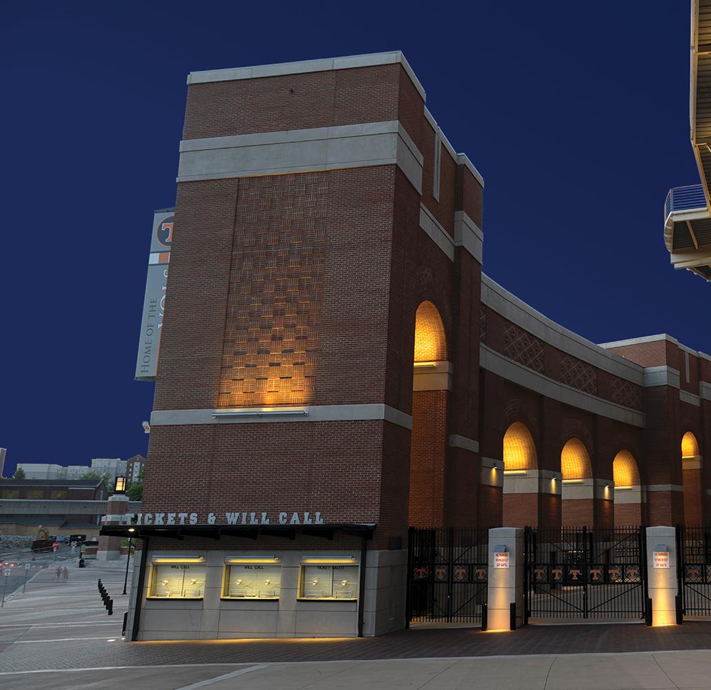Advantus linear outdoor light fixtures illuminate a brick ticket area for a college stadium at night.