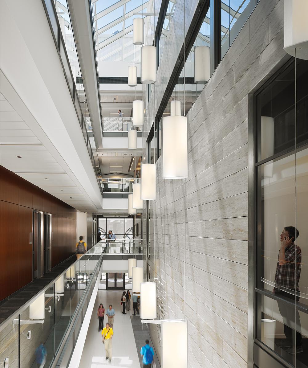 Custom light fixtures designed with Air Foil luminaires hung in tandem along a multi-floor atrium.