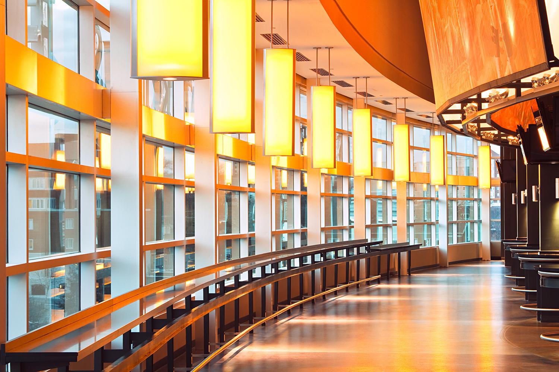 Air Foil education lighting fixtures hung along a stadium window in the university's unique orange color.