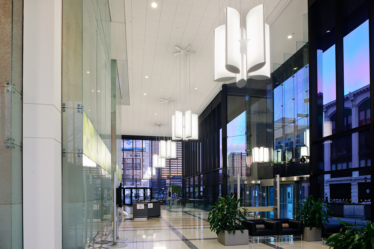 Air Foil pendants configured in multiple star-shaped clusters for stylish lobby lighting that reflects in the glass windows.