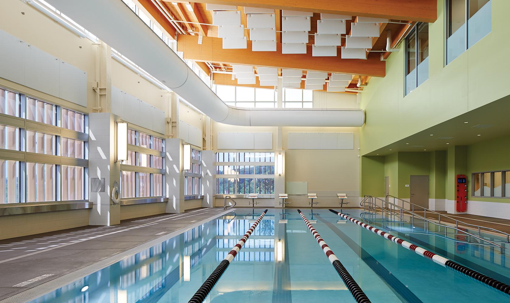 Air Foil sconces showing off modern lighting design along a well-lit indoor pool.