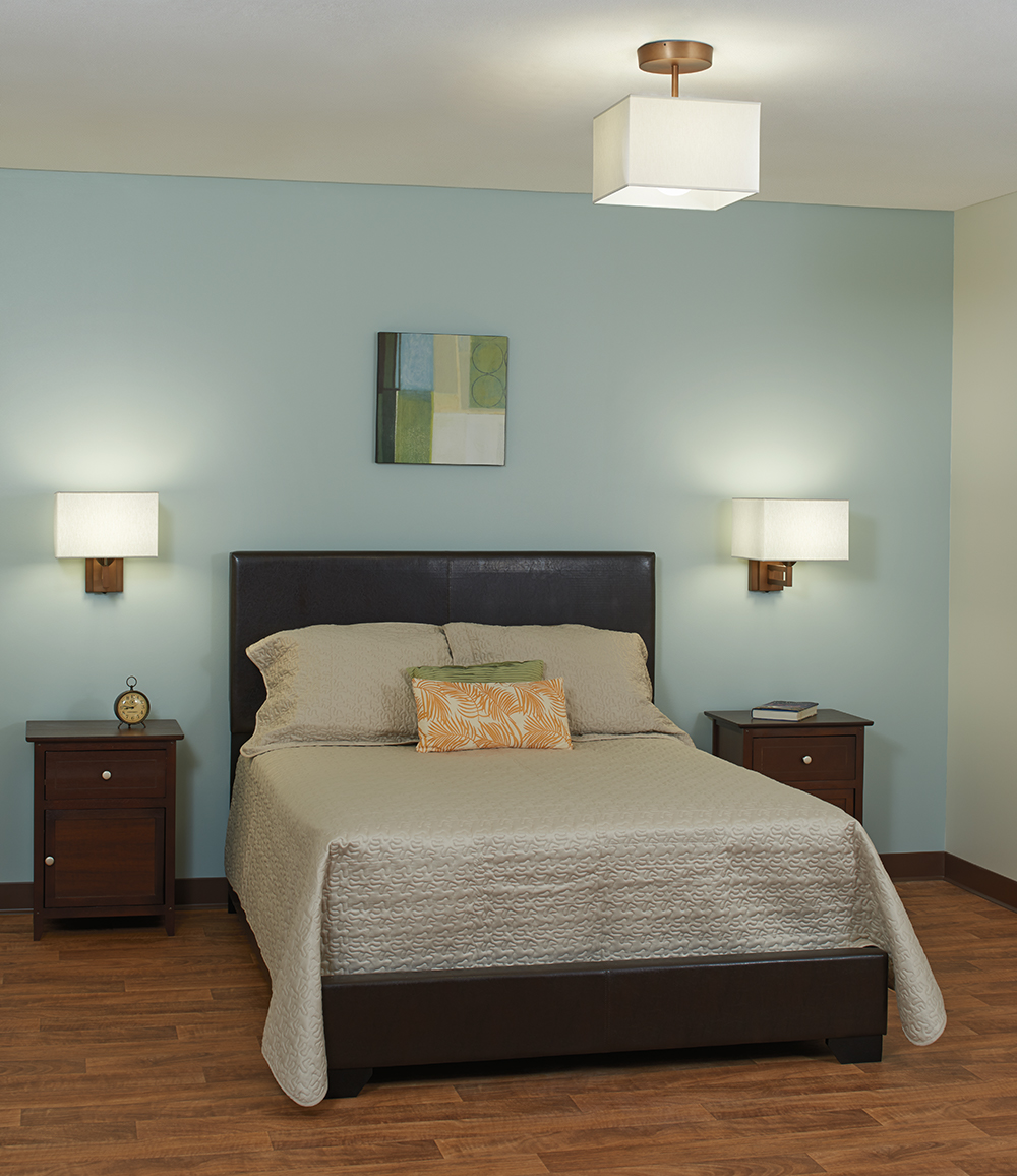 Allegro wall sconces and ceiling mounted luminaires give a multifamily design bedroom a comforting, inviting feeling.