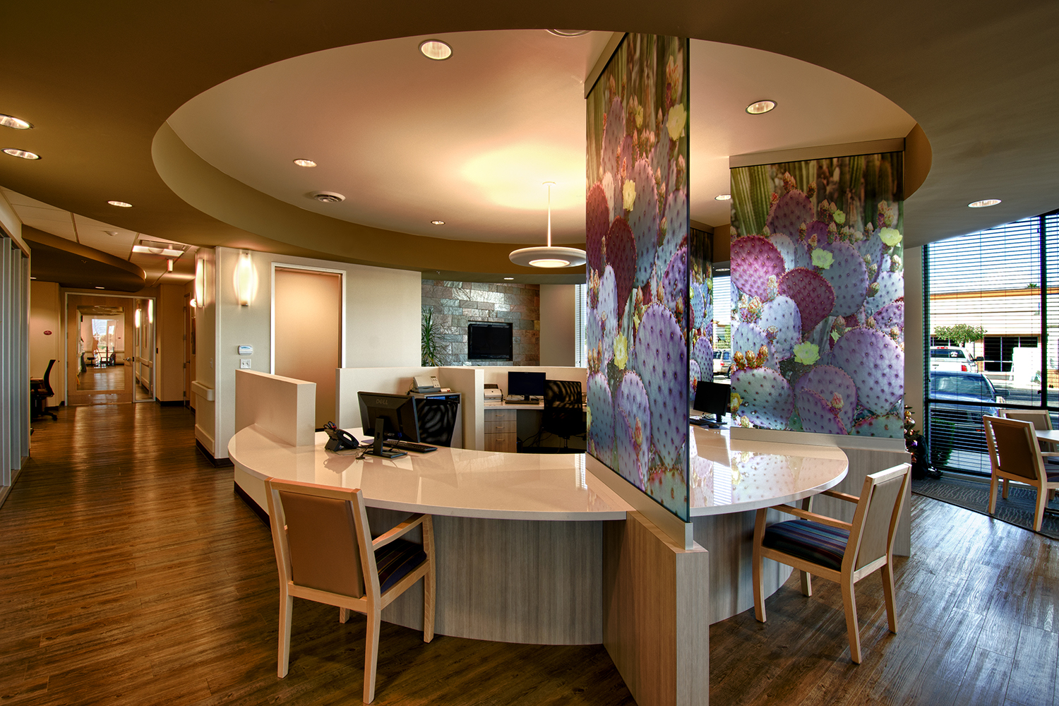 Aries pendant in a hospital lighting design above a circular, central nurses station with colorful dividing glass.