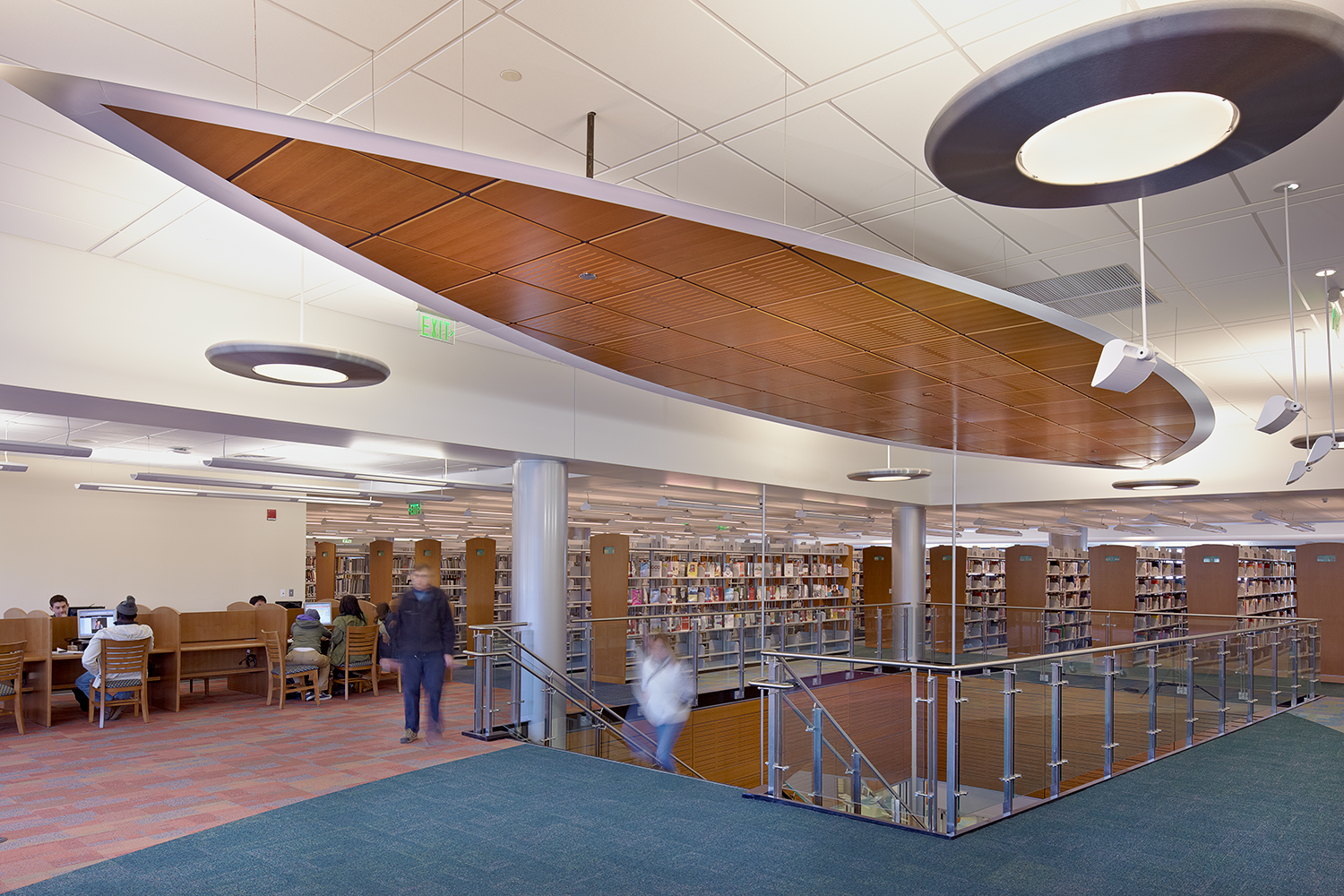Aries pendants providing modern library lighting above a wide staircase as students study.