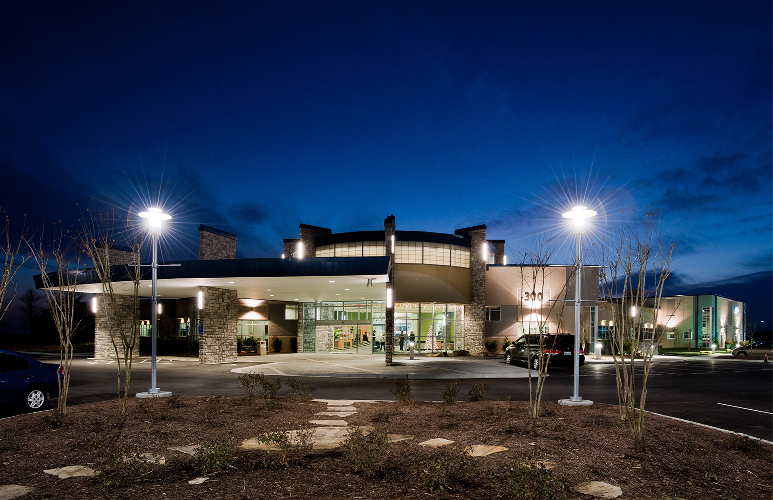 Avatar exterior lighting fixtures on a healthcare building illuminate support columns with clean, even light.