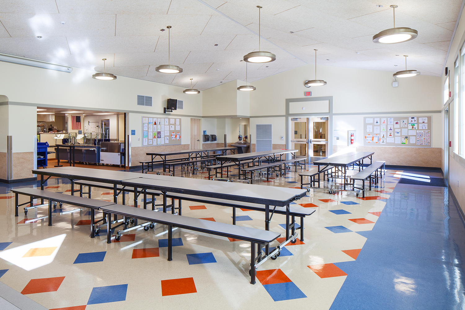 Broadway pendant luminaires as classroom lighting, hung over tables in a school cafeteria.