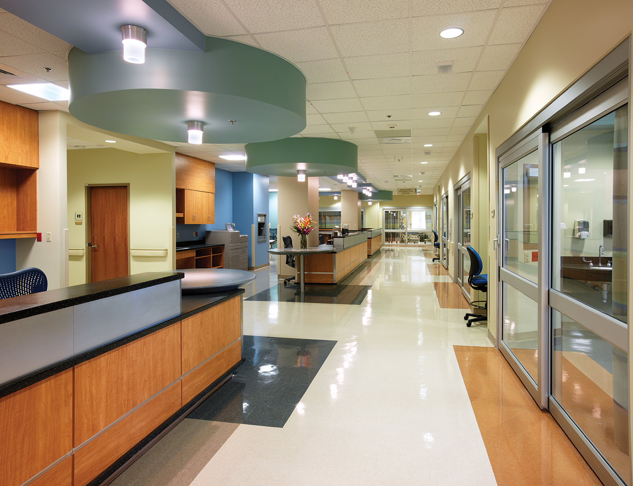 Cane ceiling luminaires in a clean hospital design illuminate a nurse's station.