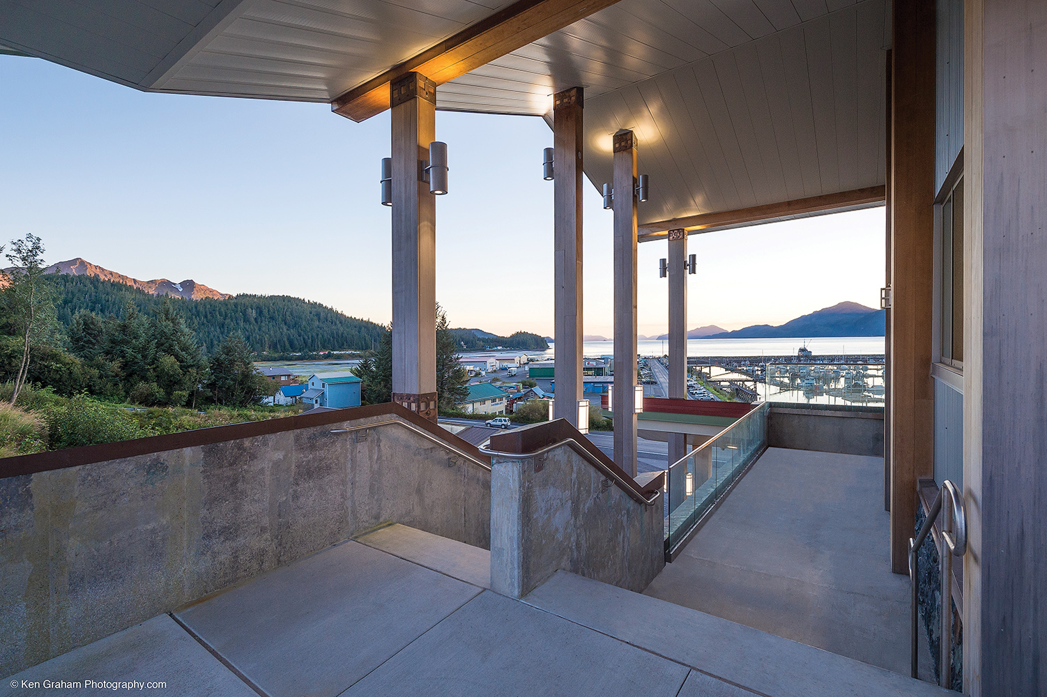 Colonnade and Scope outdoor lighting fixtures illuminate the support columns of a beautiful waterfront building.