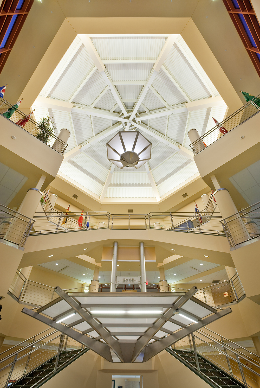 Large, geometric custom light fixtures hang from an open multi-level atrium.