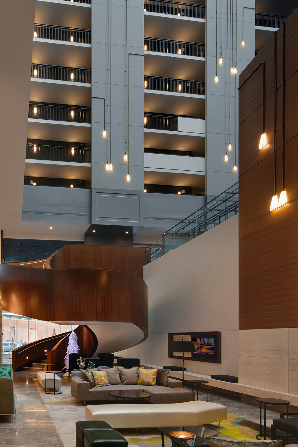 Unique, A-shaped custom light fixtures with square-angled black connecting pipes in a hotel lobby.