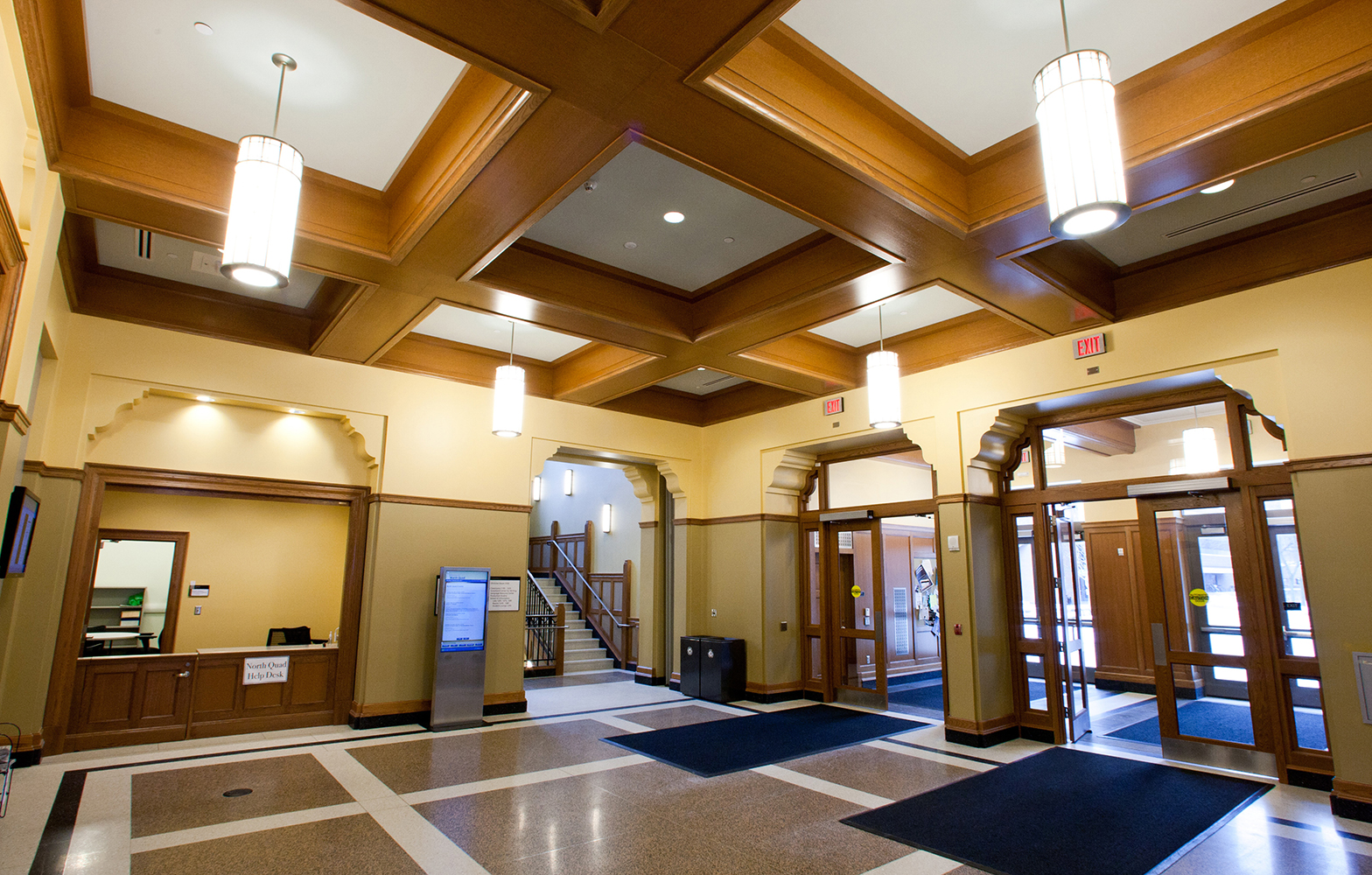 These cylindrical custom light fixtures illuminate a campus entryway with wooden ceiling beams.