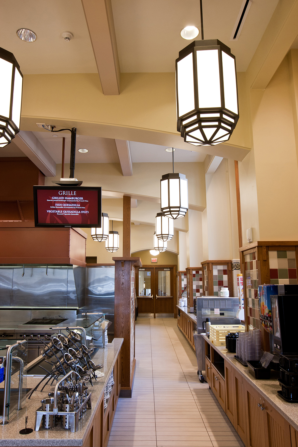 Bold, lantern-style custom light fixtures lined above a clean, classically styled campus kitchen.