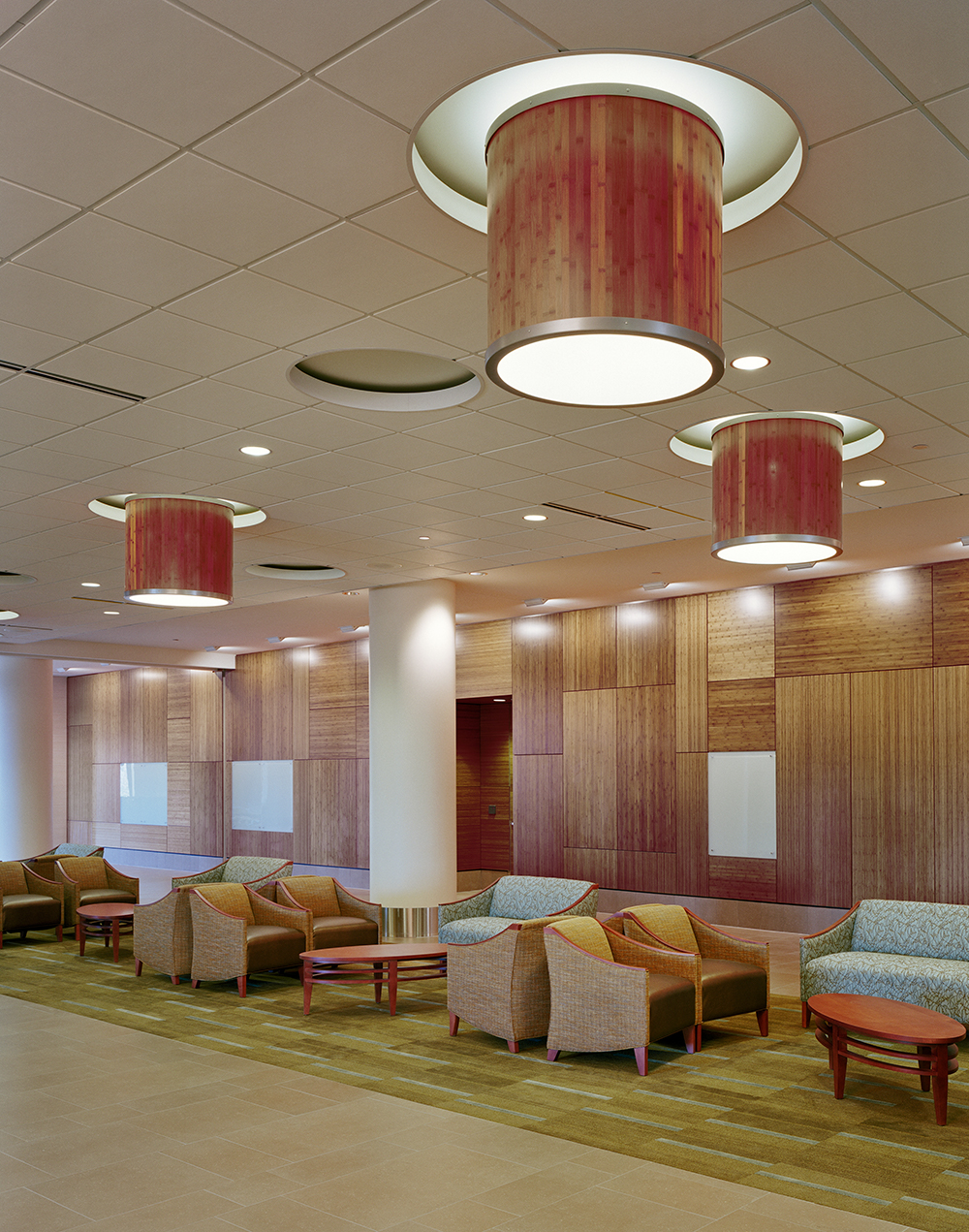 Large, wood-paneled custom light fixtures mounted above a warm waiting room.