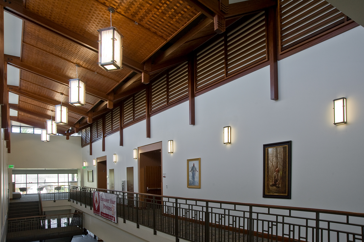 Distinguished custom light fixtures with heavy columns and frames in a university hallway.