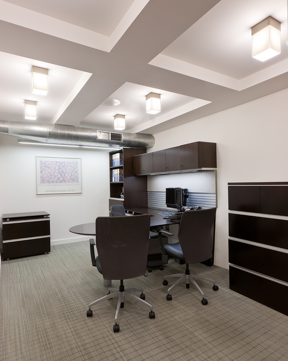 These custom light fixtures are clean, rectangular downlights for a sophisticated white and brown themed office.