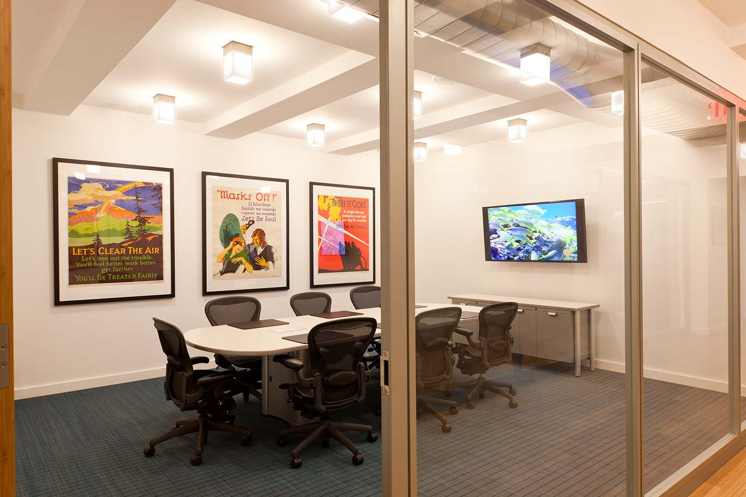 These custom light fixtures are clean, rectangular downlights for a sophisticated office conference room.