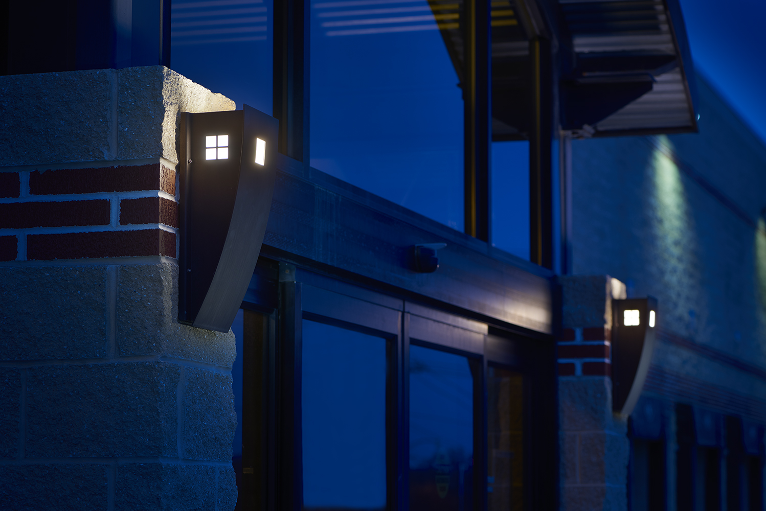 Cypress outdoor light fixture illuminates a dark exterior doorway, with small window cutouts on the side of the luminaire body.
