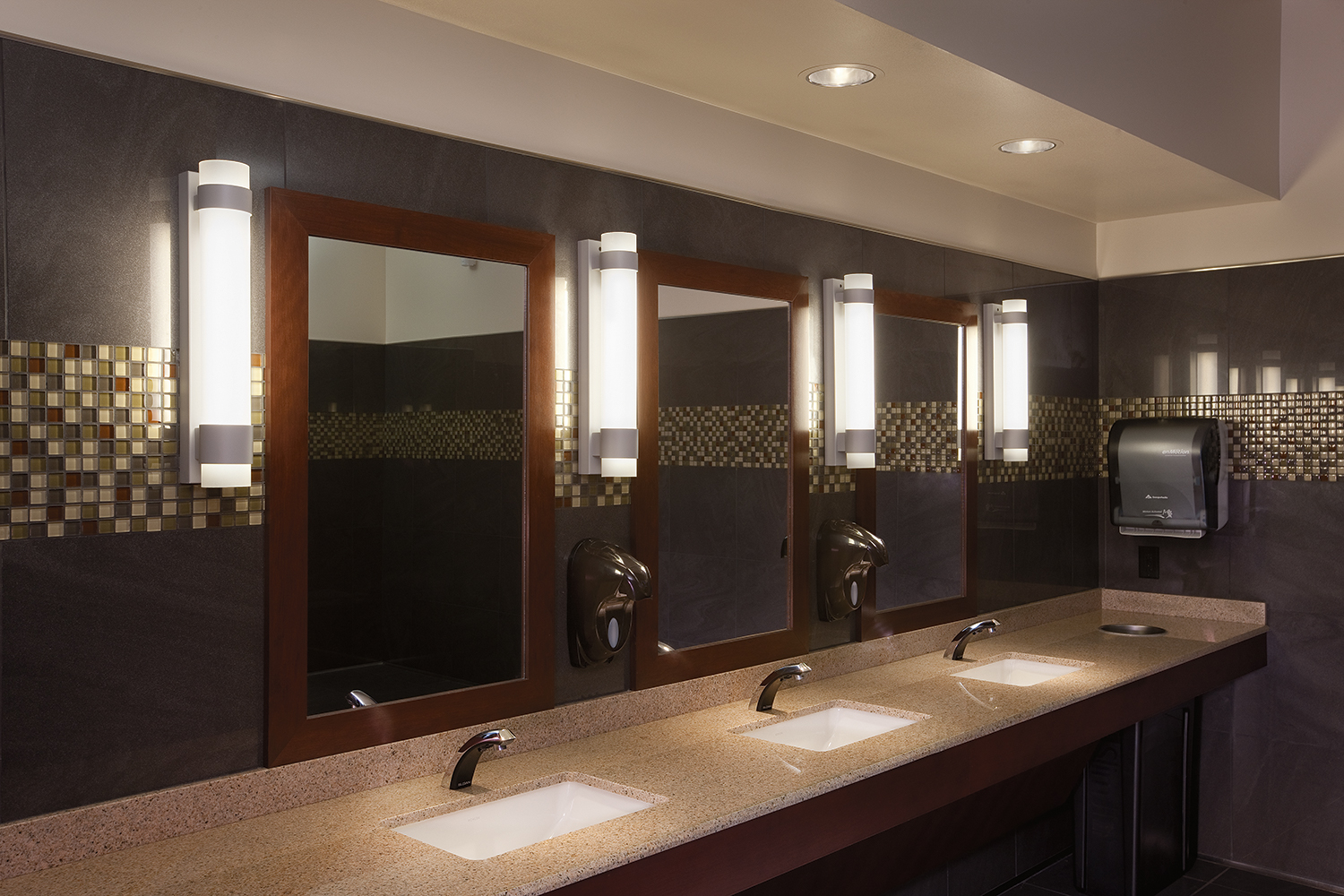 Flambeau vanity light fixtures mounted vertically between mirrors in a modern public restroom