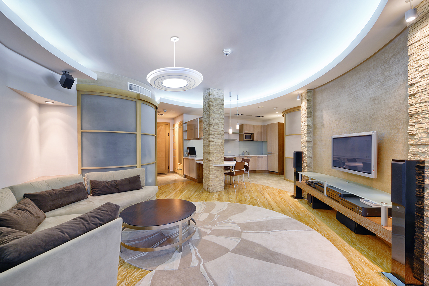 Gemini pendant in an apartment lighting application above a large, circular living room with stone walls