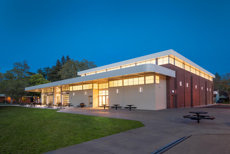Image exterior lighting fixtures illuminate a school building at night.