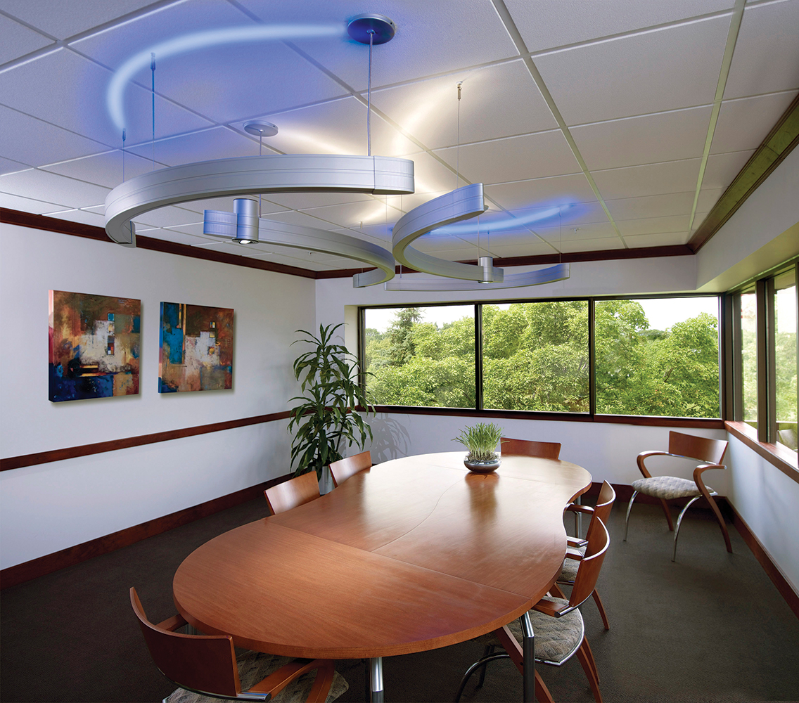 Infinity Art curved linear suspended office lighting fixtures emit blue light above a rounded conference table.