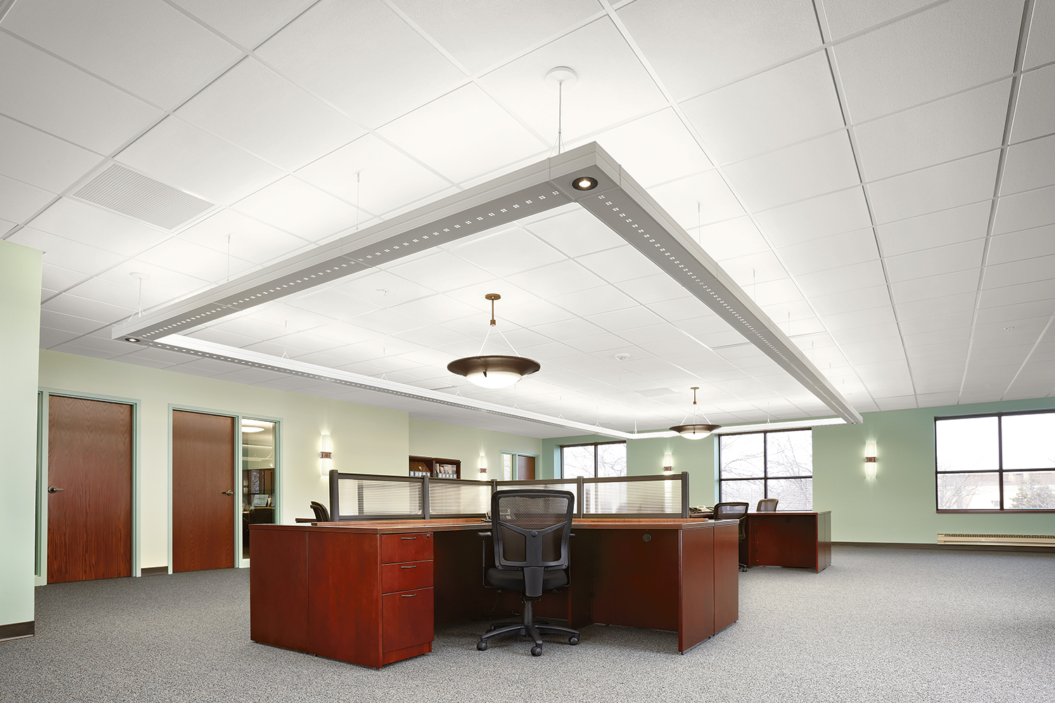 Infinity Performance large linear suspended luminaires in a rectangular configuration above an open office with Pila sconces.