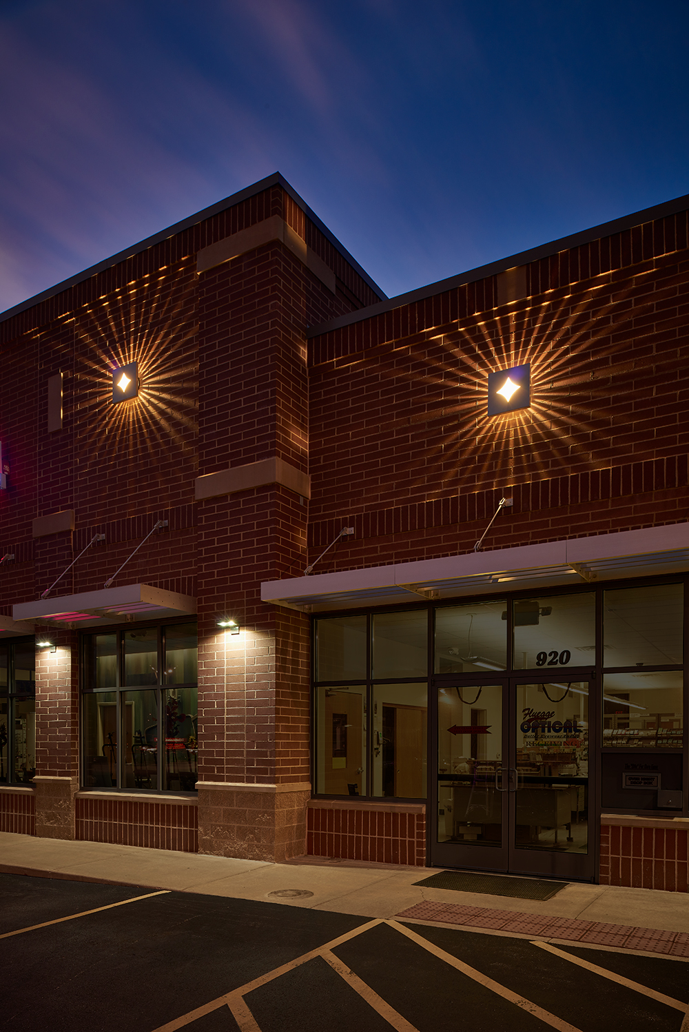 Lightshower outdoor light fixtures display a pattern of light across a store exterior at night.