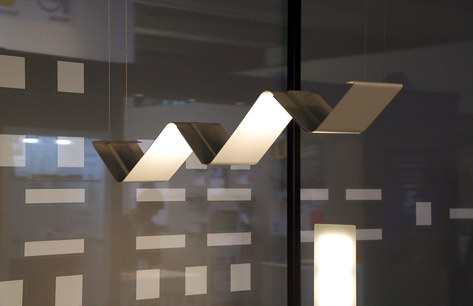 Limit pendant in an office lighting application, close-up of the OLED light reflected on the zigzag panels.
