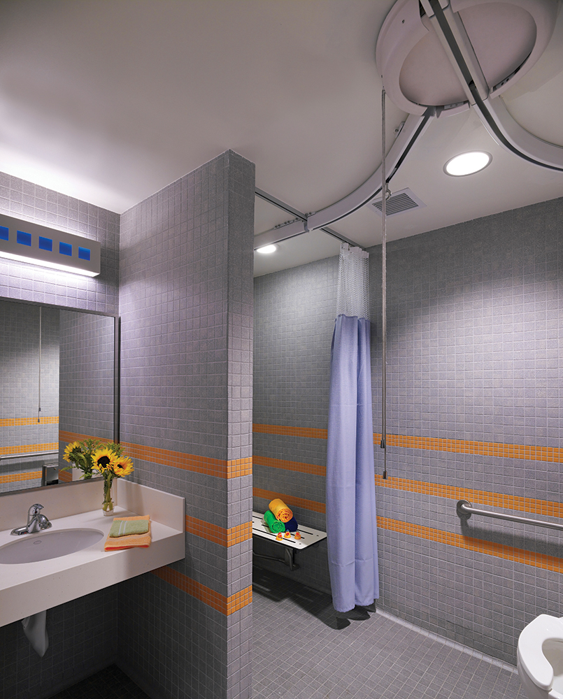 Linear Art Sconce vanity light fixture with blue accents, mounted horizontally above a wide patient room mirror.