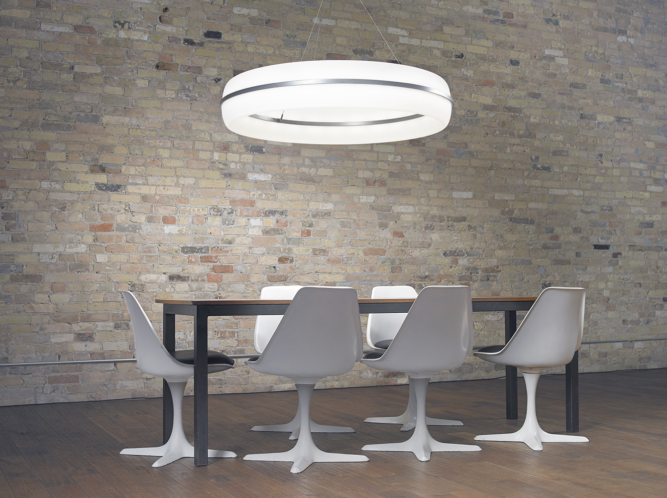 Meridian Round pendant is perfect for office lighting, seen here above a sleek conference table near a brick wall.