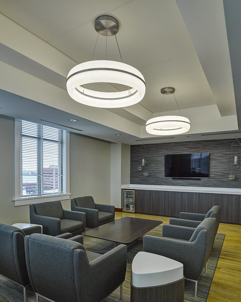 Meridian Round pendant is perfect for office lighting, seen here above a comfortable meeting area in a modern design office.