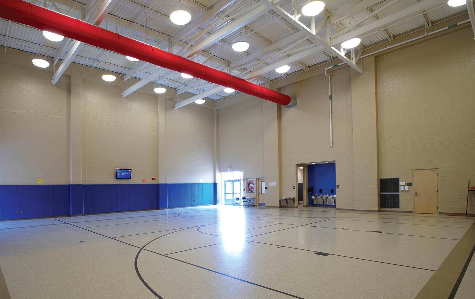 Midbay, a large light fixture for industrial and large venue applications, works well for this school gymnasium.