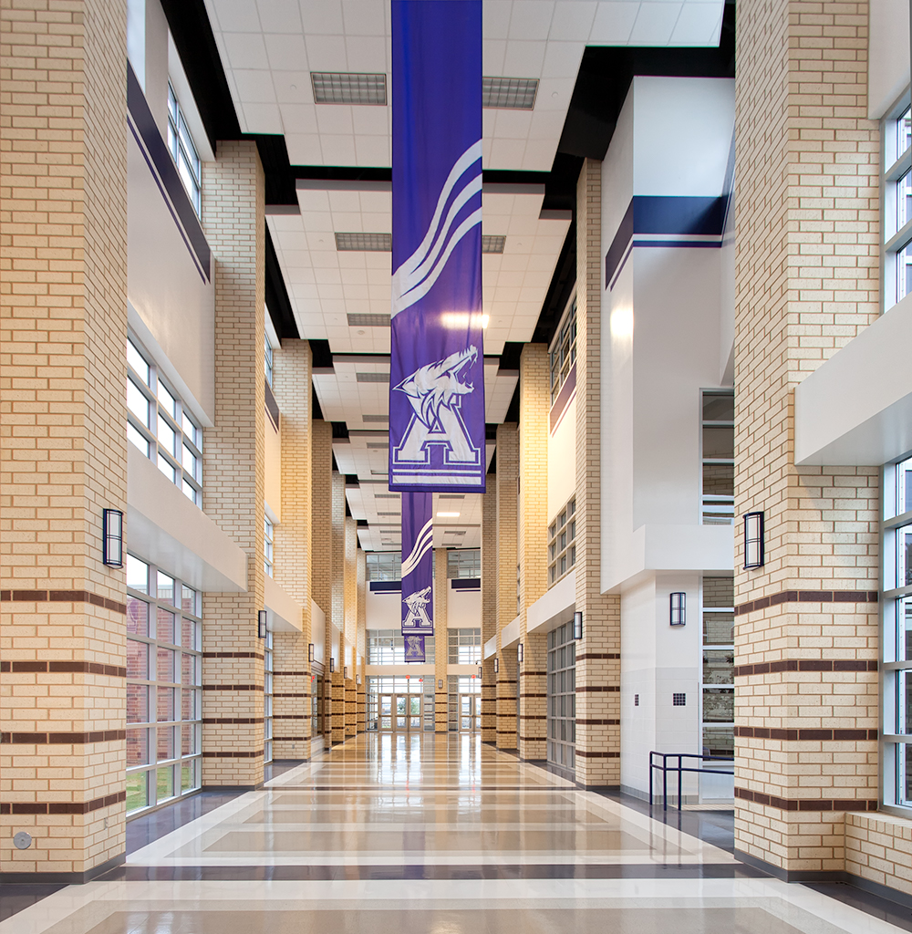 Midland Arts timeless wall sconces in an education lighting application along a campus sports facility corridor.
