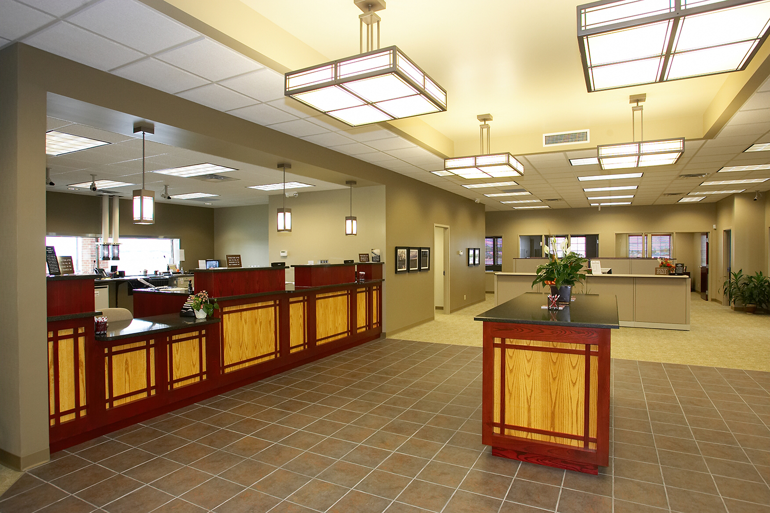 Midland Crafts architectural lighting fixtures illuminate a sophisticated bank lobby.