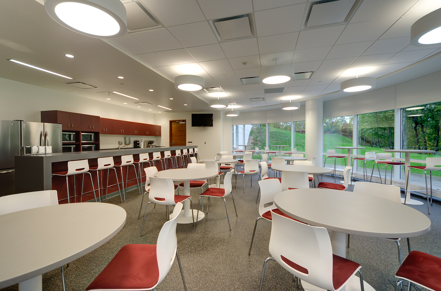 Omnience office lighting fixtures in a workplace cafeteria with round tables and large windows.