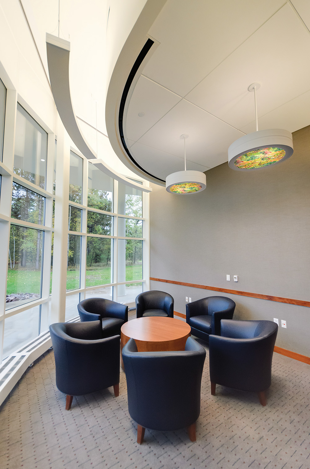 Omnience office lighting fixtures with Vara Kamin diffusers over a small meeting area near large windows.