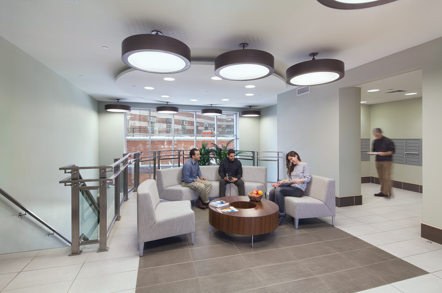 Omnience office lighting fixtures in a common seating area between a stairwell and a mailroom.
