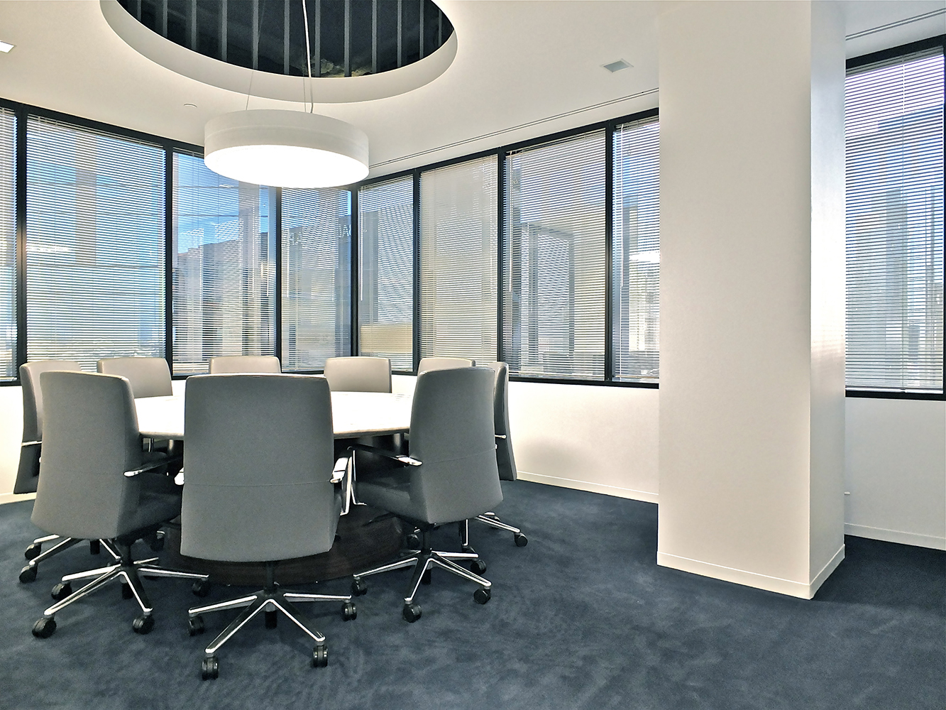 Omnience office lighting fixtures are perfect for conference tables, seen here above a small round table near large windows.
